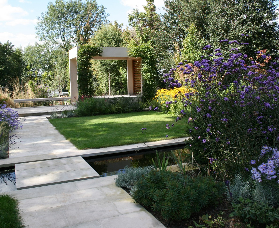 An arts and crafts garden with purple flowers, canal and shelter