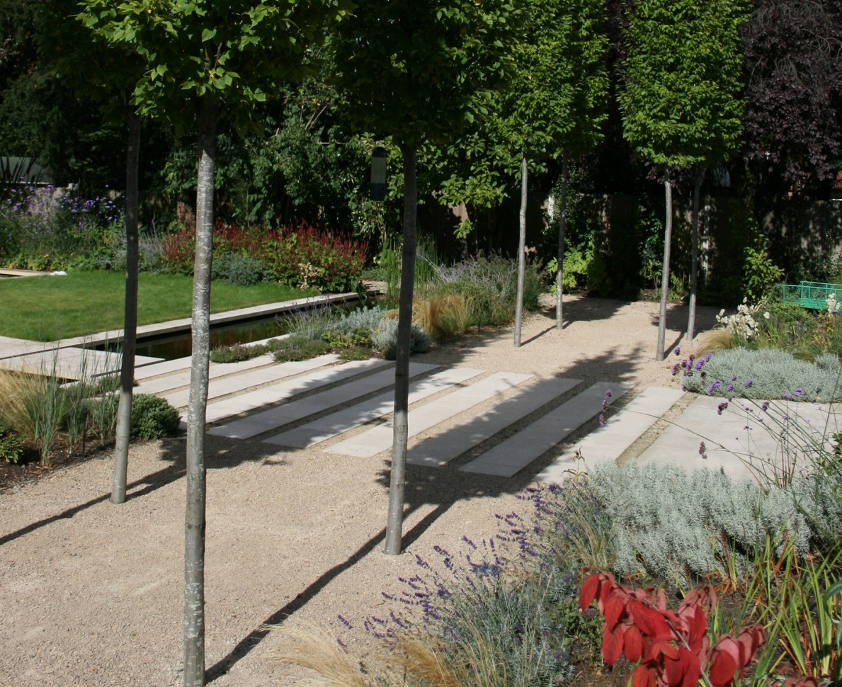 A tree lined path in the arts and crafts themed garden