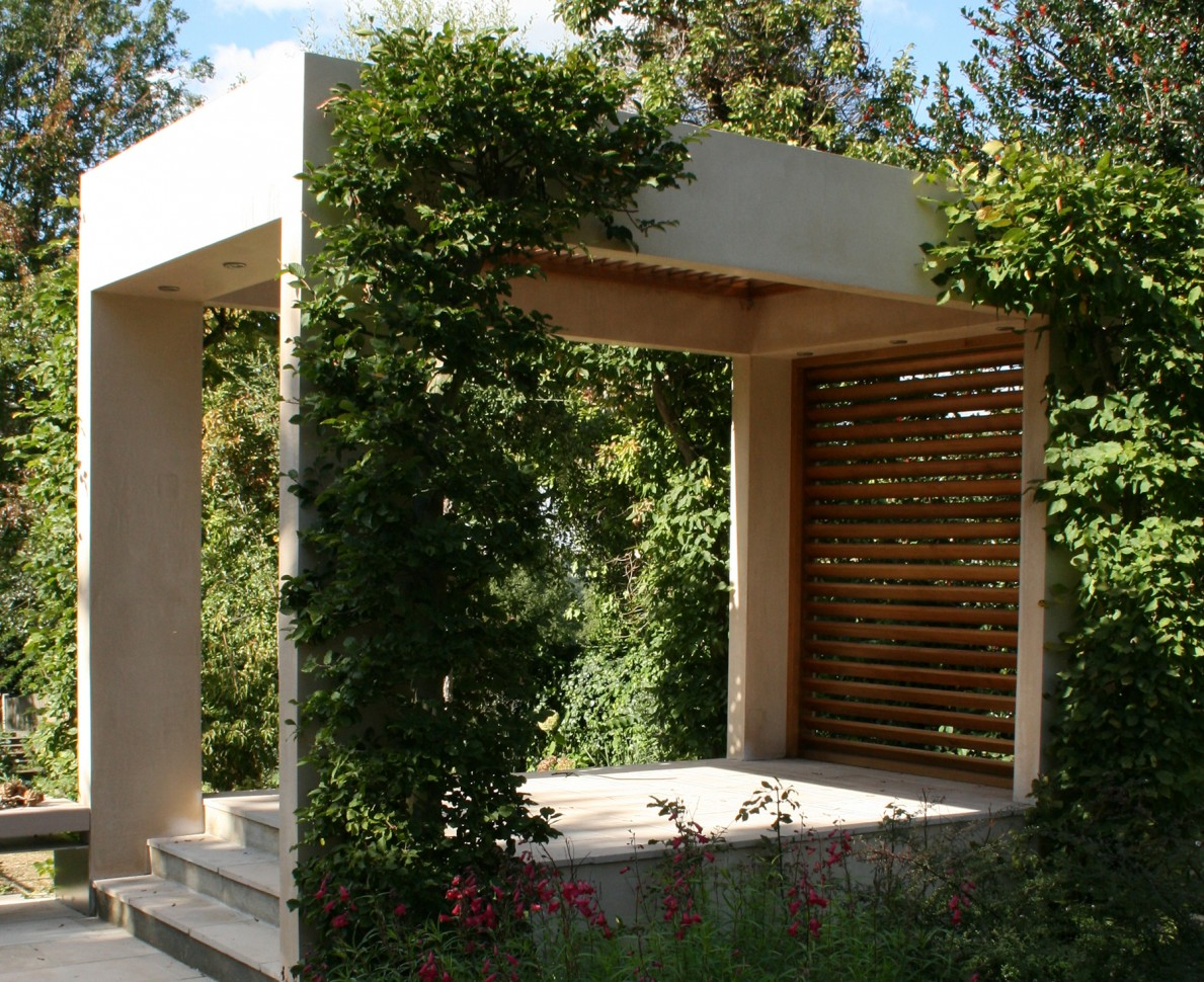 A view of the modern shelter with climbing plants in the arts and crafts themed garden