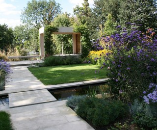 Formal arts and crafts style garden with paths and a canal running across it