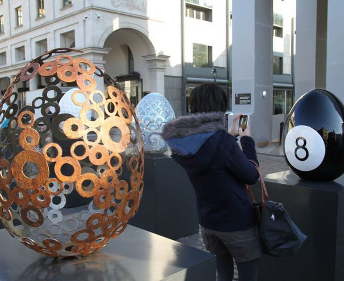 Egg on display alongside other eggs at the Faberge Big Egg Hunt 2012, with a lady taking a photograph