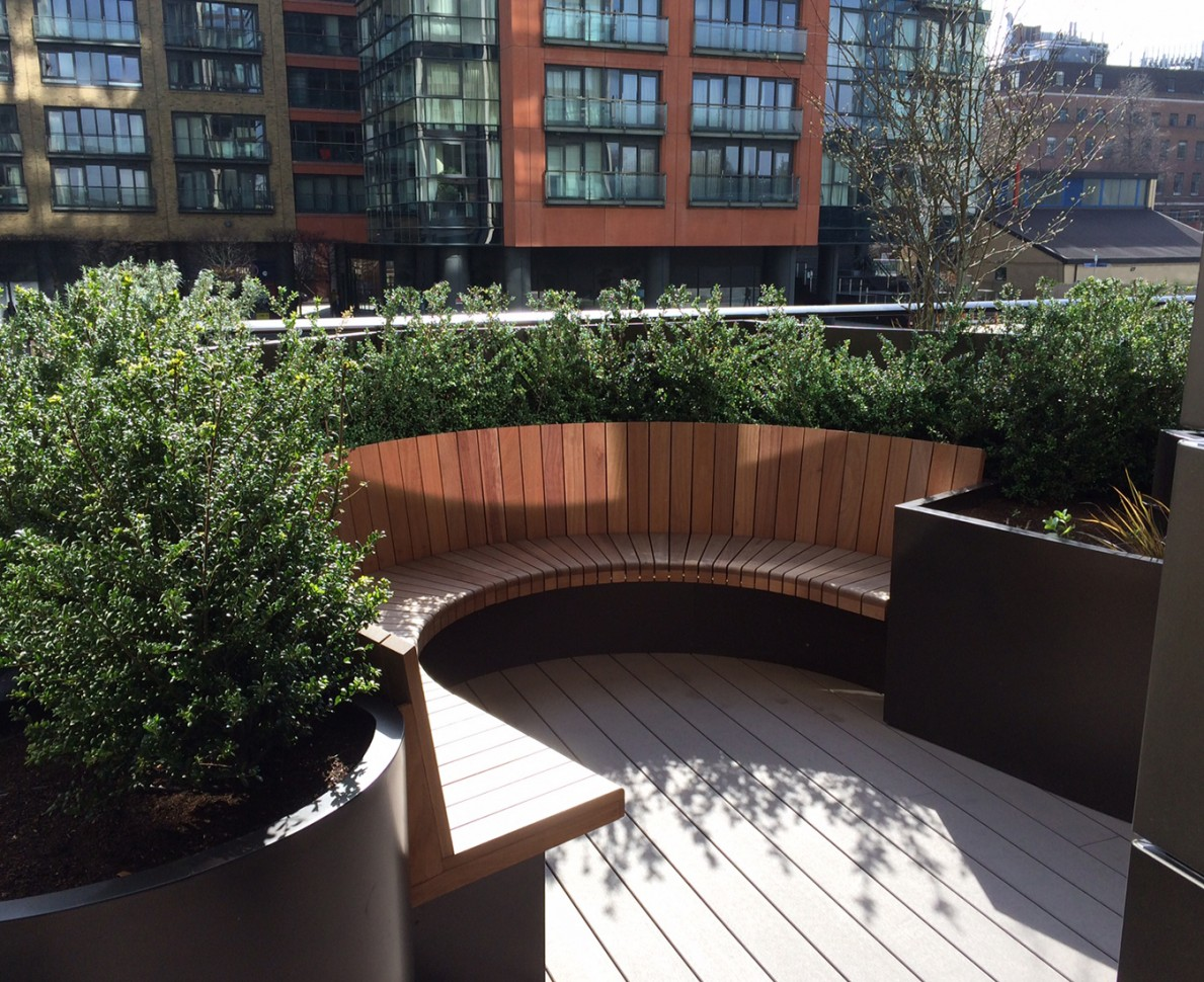 Curved wooden seating area with bushes and large planters
