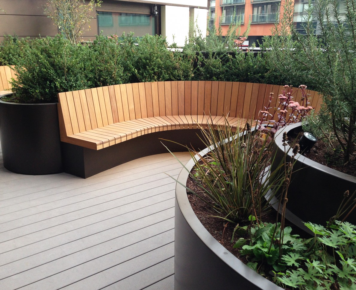 Curved seating and planters with evergreen hedges