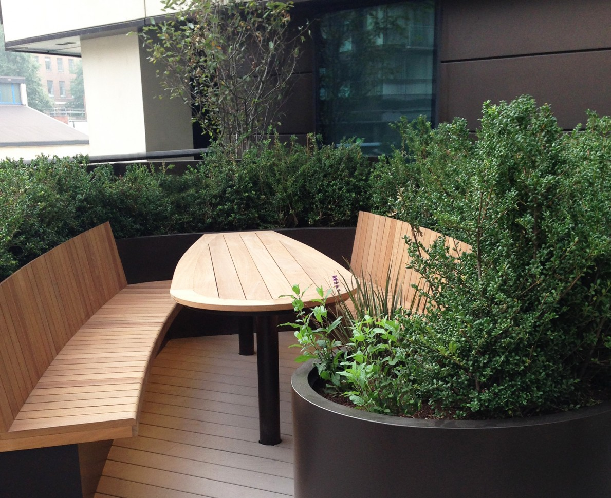 Bench and table area at Merchants Square with evergreen hedges surrounding it