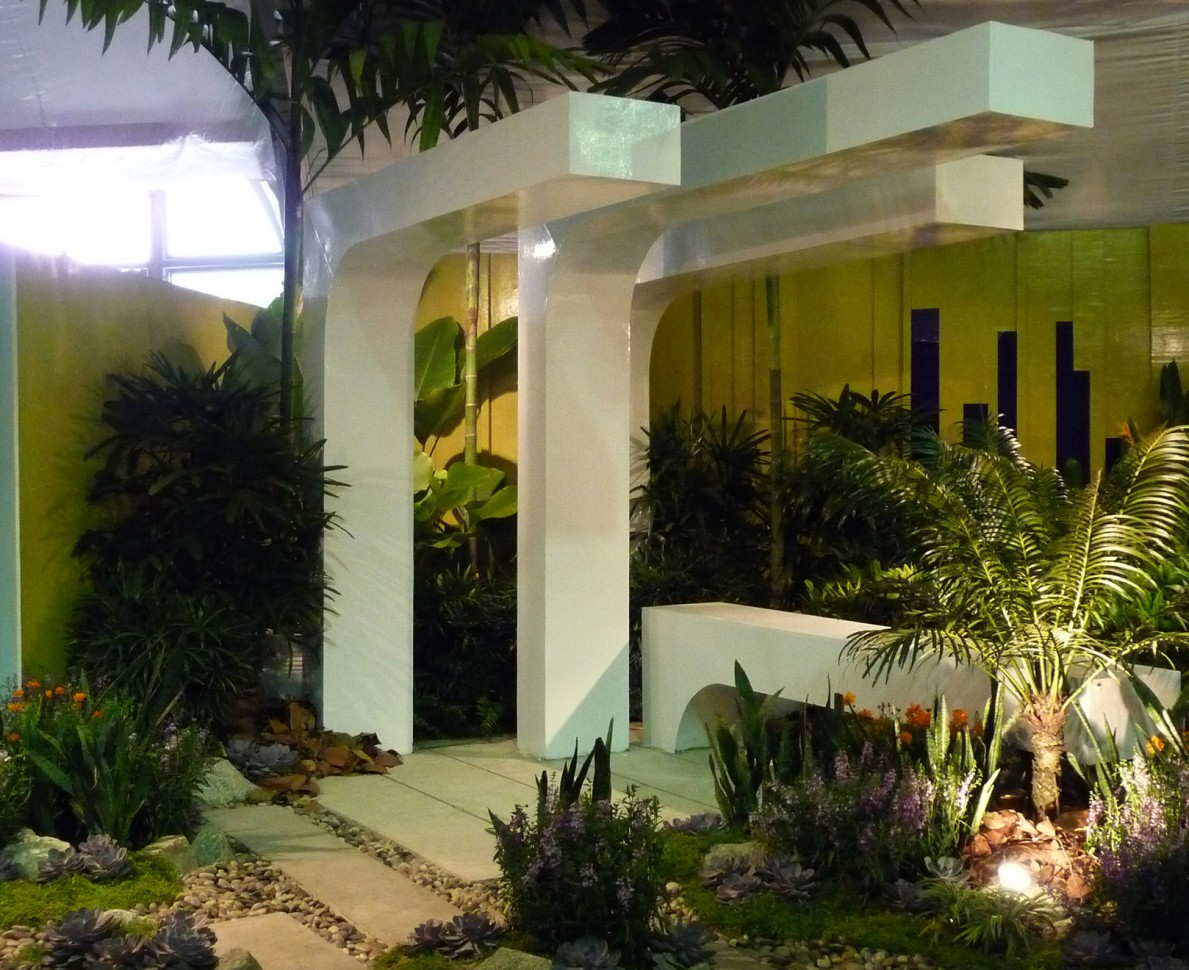 Tropical plants against the modern pergola with a bright yellow background