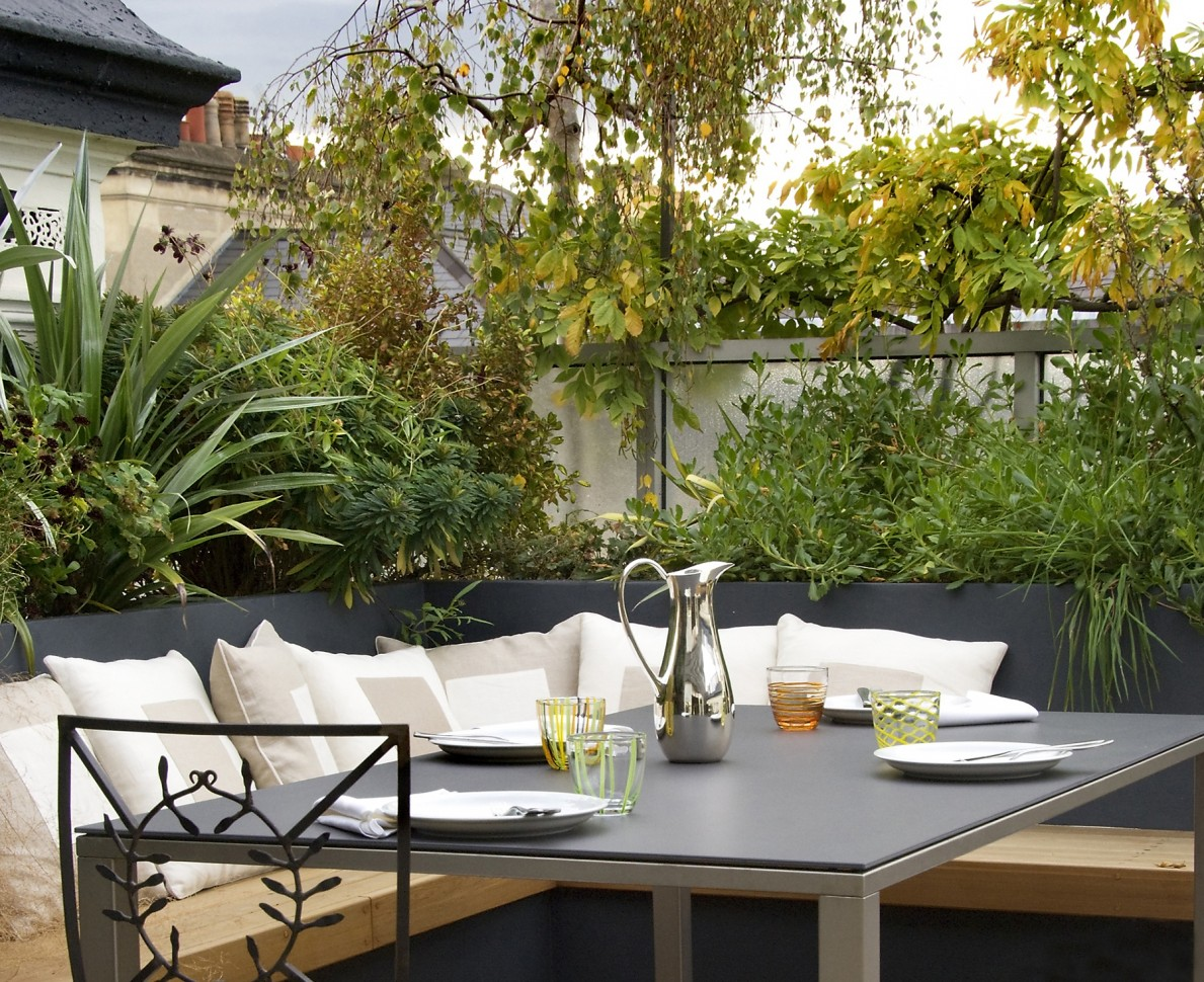 View of the outdoor dining area with comfy cushions and bright greenery surrounding