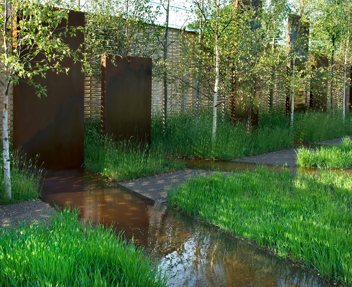 Water features between the fields of wheat leading towards the corten monoliths