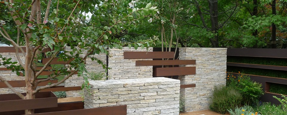 Linear stone and metal sculptures embracing the trees in the Gardening World Cup 2010 garden