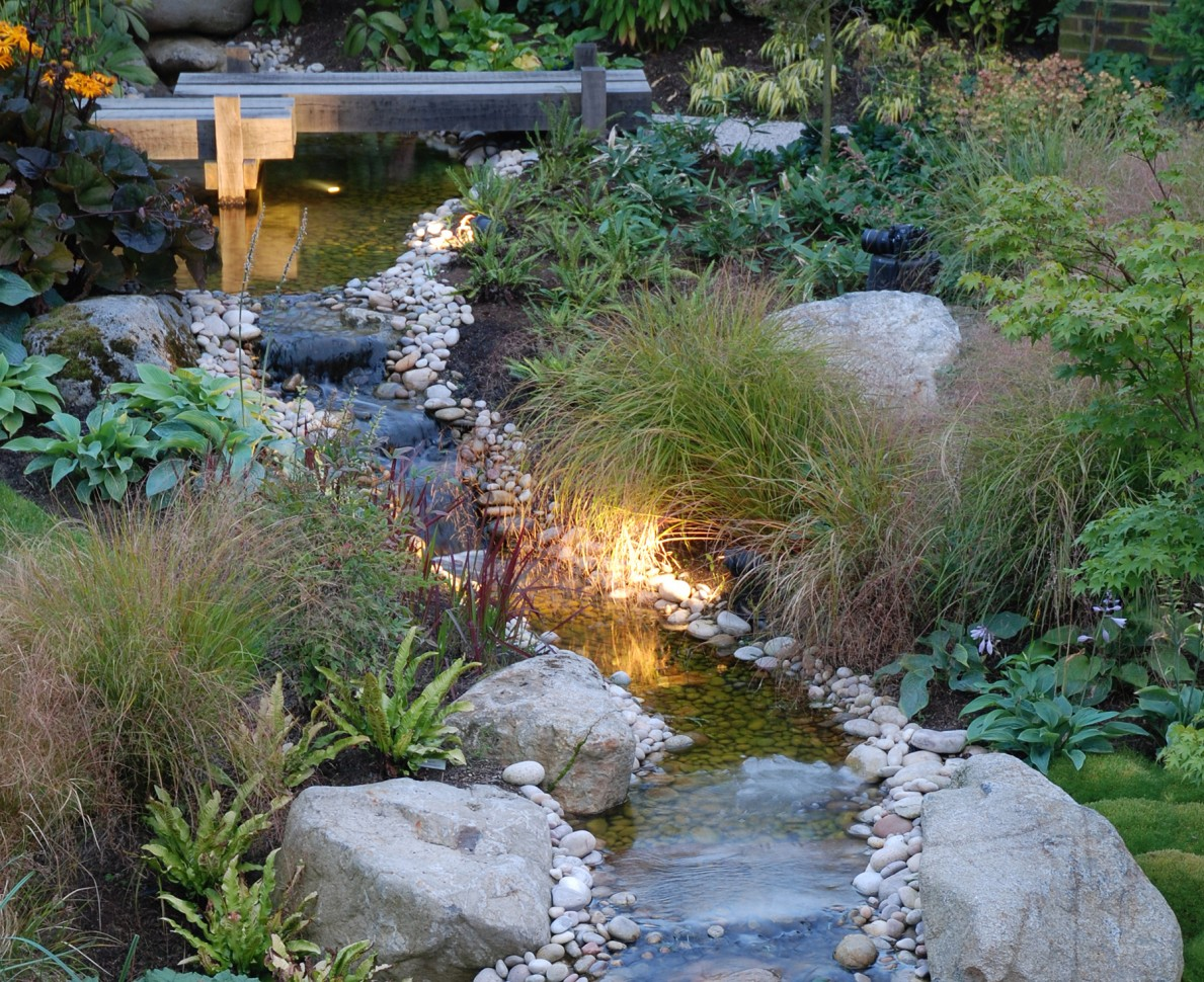 Water feature with wooden bridge and surrounded by stones, grasses and plants