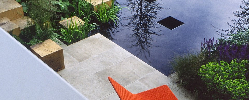 Modern Garden With Two Orange Chairs Wooden Block Rock Garden With Green Plants. Modern Water feature With Reflection Of Tree