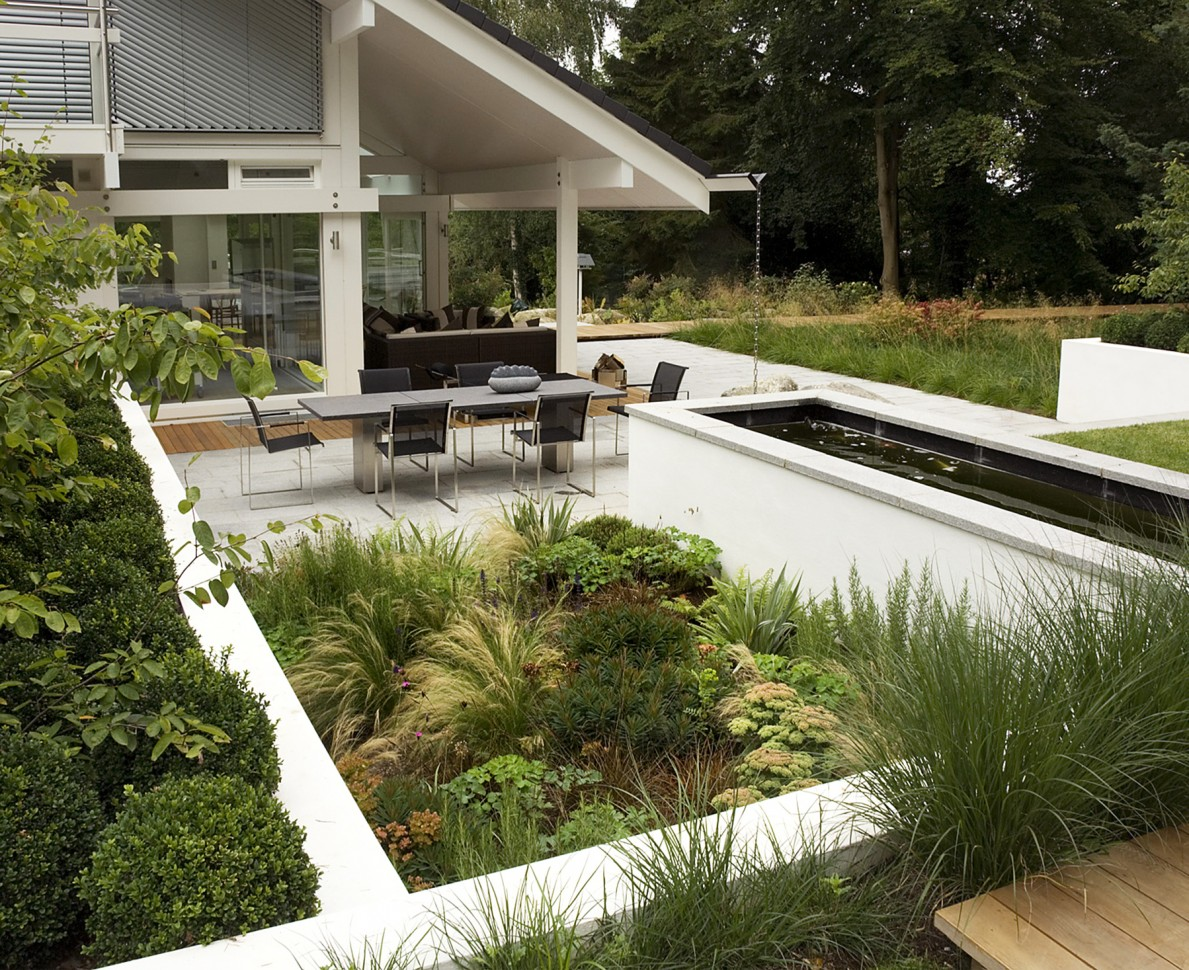 White walled planting areas filled with green shrubs and grasses