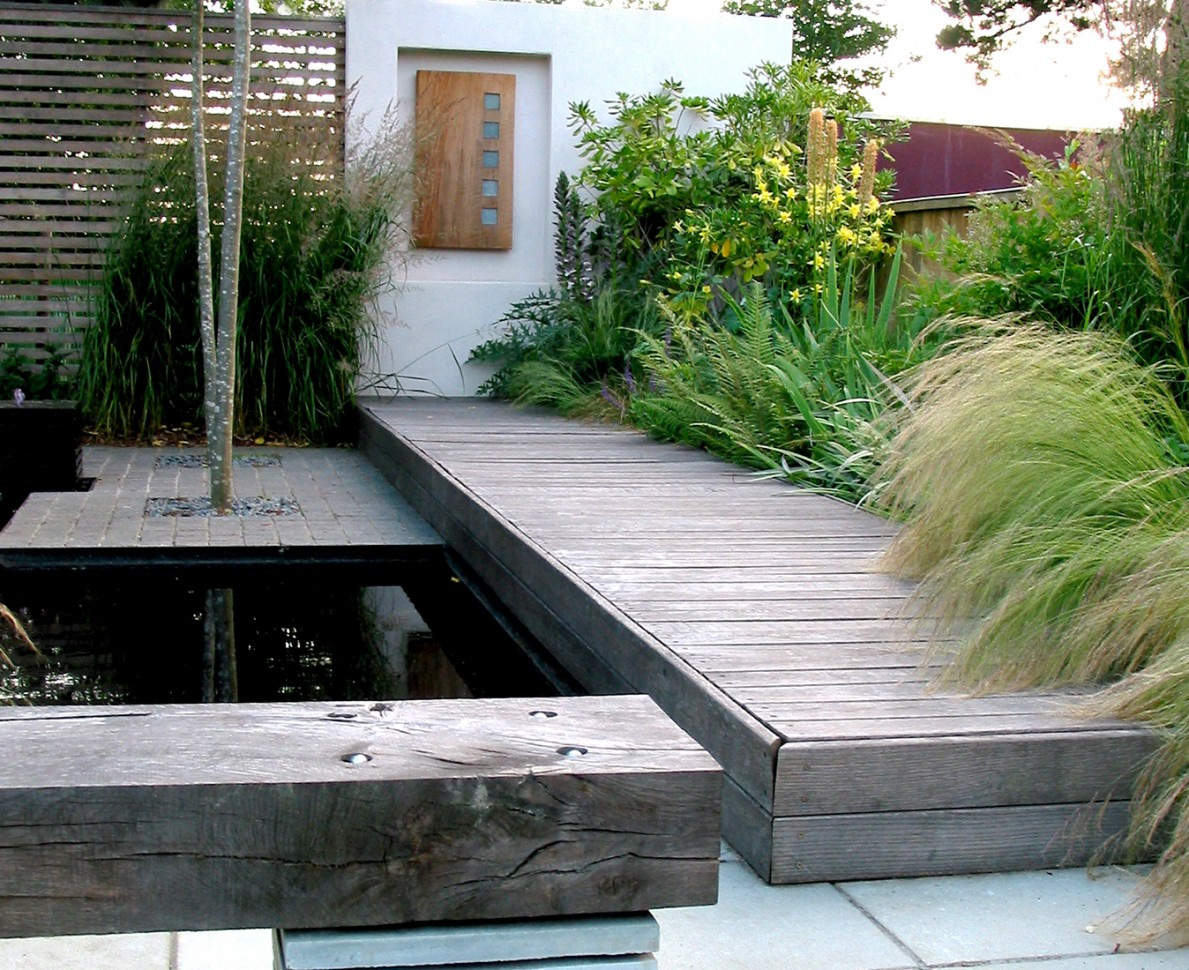 Bench made from a sleeper by a water feature and decking