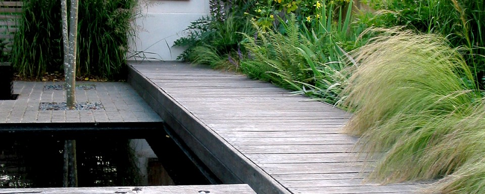 Wooden Decking Next To Water Feature And Bed Of Green Plants