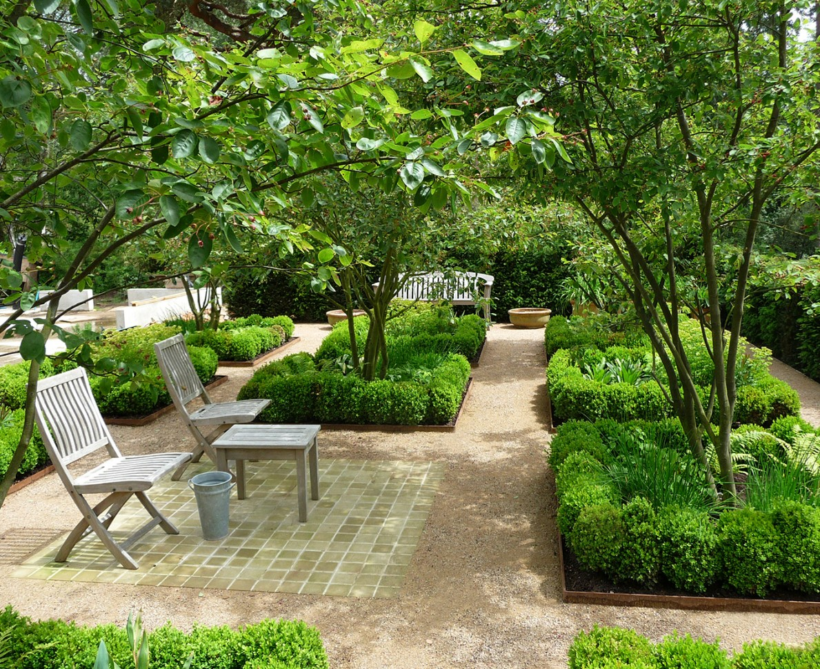 Wooden chairs in a parterre garden room with trees and herbs