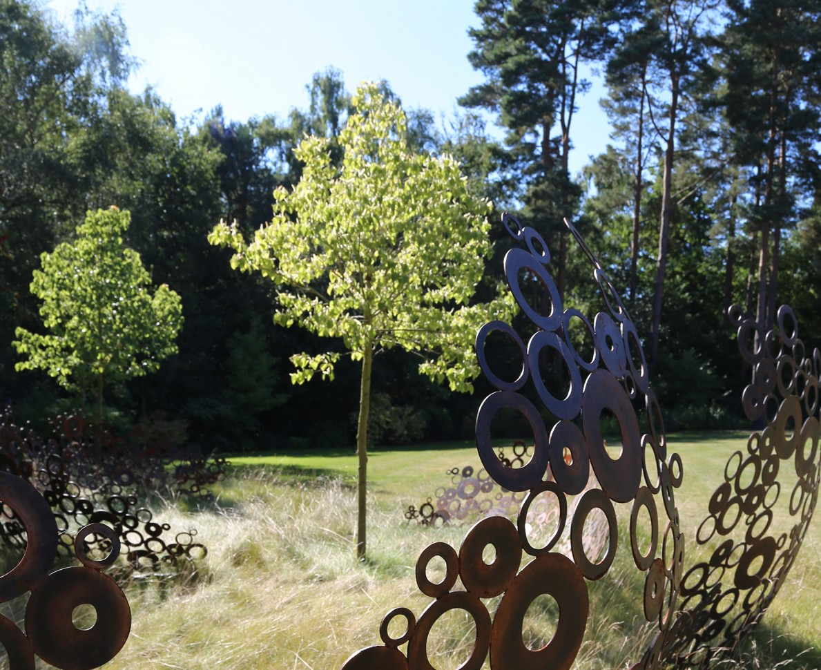 Tree surrounded by sculpture made of metal circles