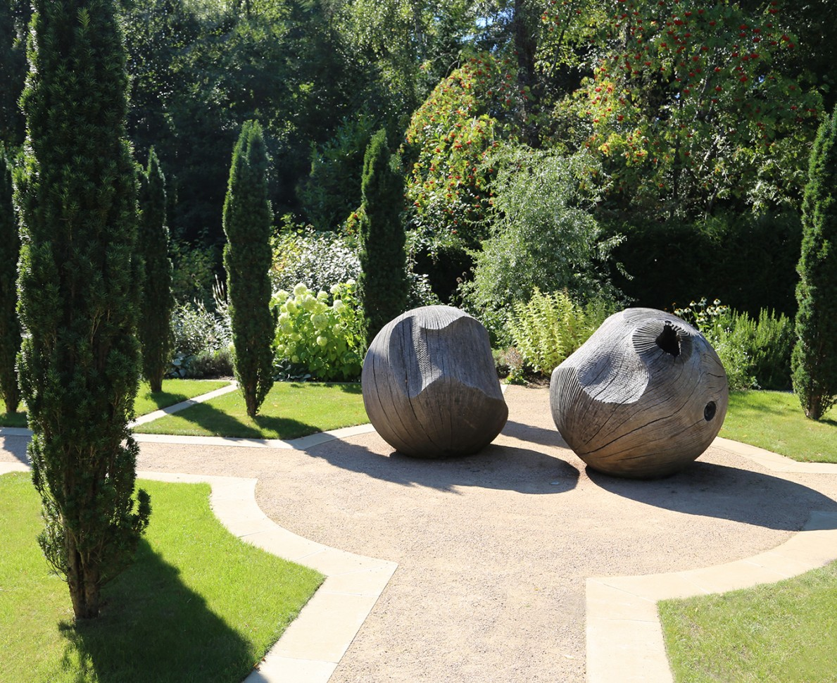 Two wooden sculptural ball shapes surrounded by trees