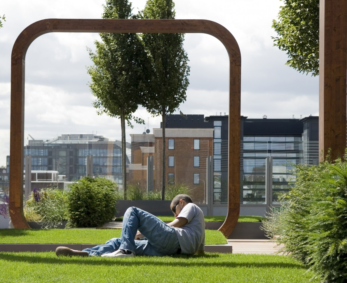 Man relaxing on the grass framed by a wooden arch