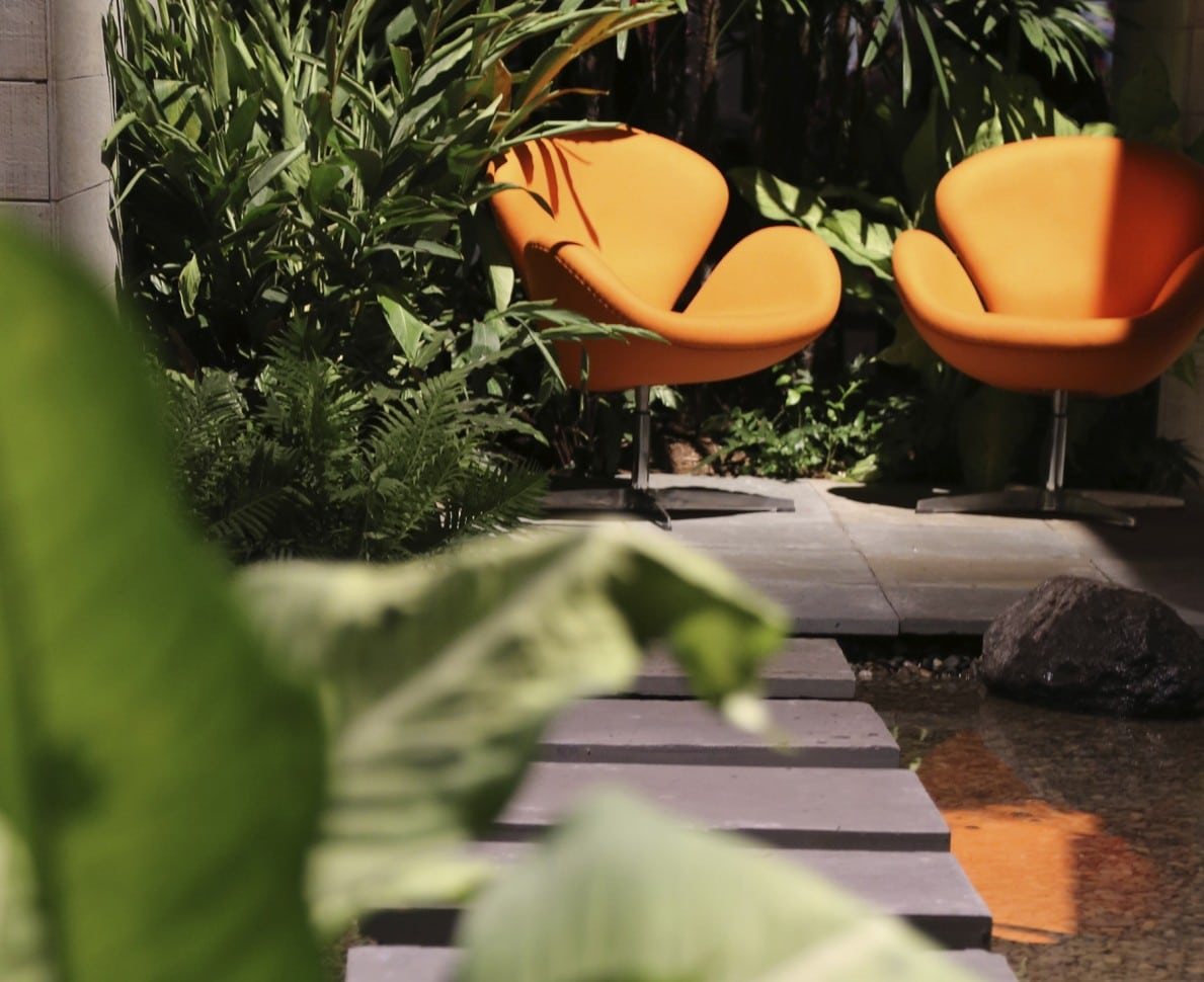 View down a stepping stone path to two orange chairs