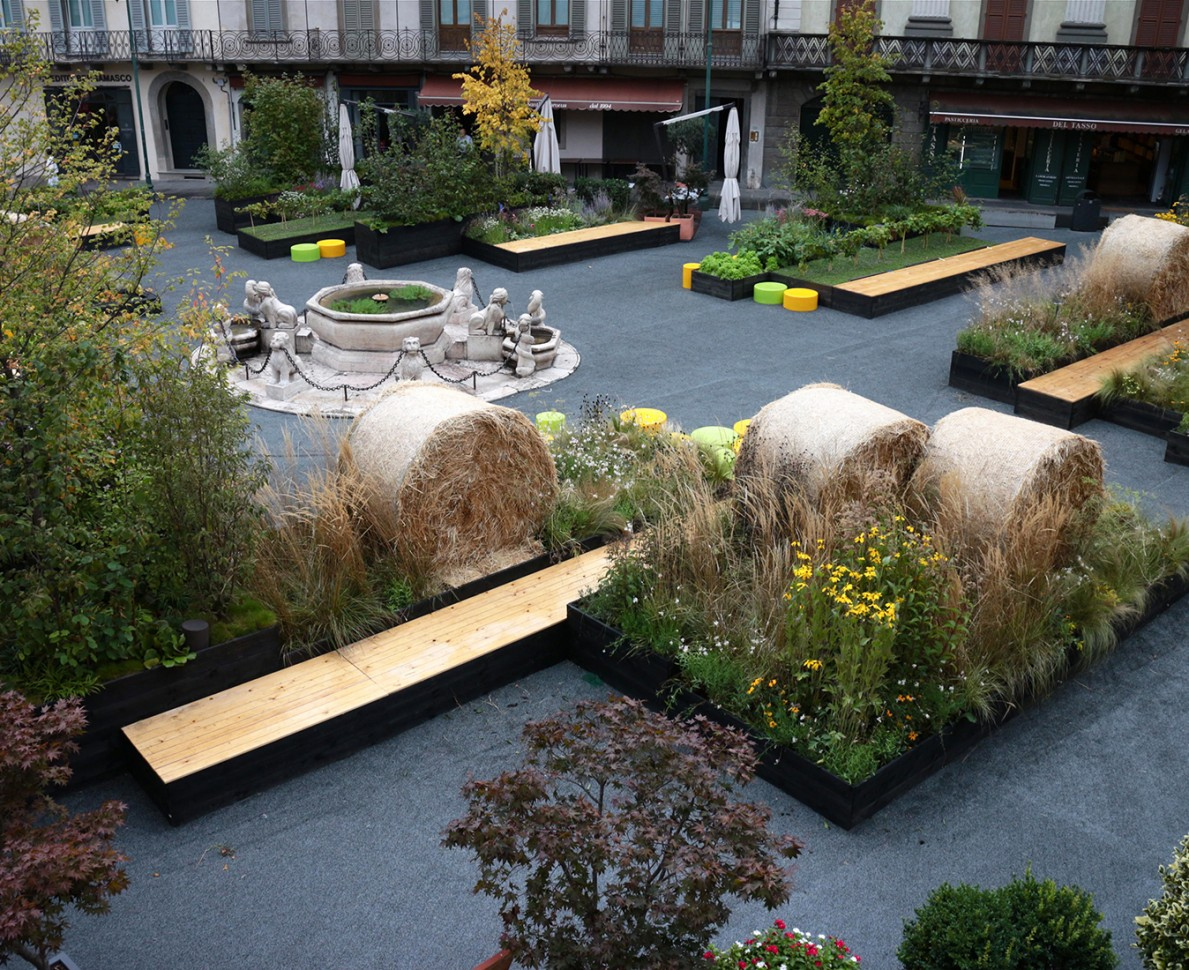 Boxes of planting with haybales, benches and a water feature