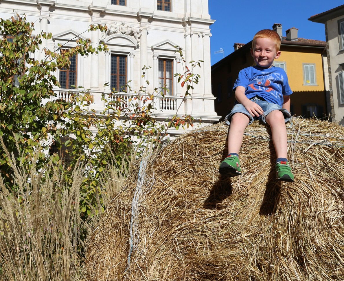 A child sits on a haybale in the piazza