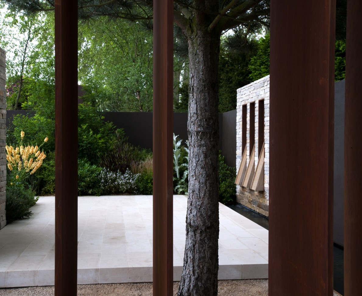 Looking through metal bars to the garden beyond with marble floors and stone walls contrasting the planting