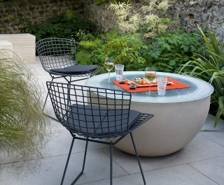 Unusual seating area with round glass table, set for a sushi meal in a small studio garden