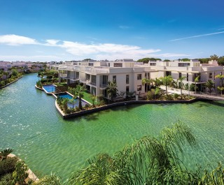 Modern Building Complex With Clear River Surrounding Featuring Palm Trees And Swimming Pools