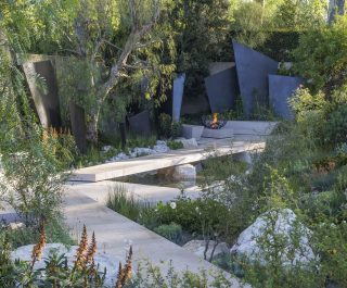 The Telegraph Garden Pathway With Stone Sculptures And Green Shrubs