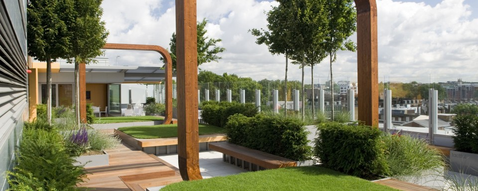 Modern City Rooftop Garden Featuring Squares Of Grass Surrounded By Wooden Decking With Seating Area And Wooden Arches
