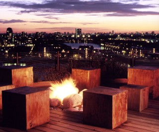 Roof garden with cube seating surrounding a firepit, looking out over London Docklands during a stunning sunset
