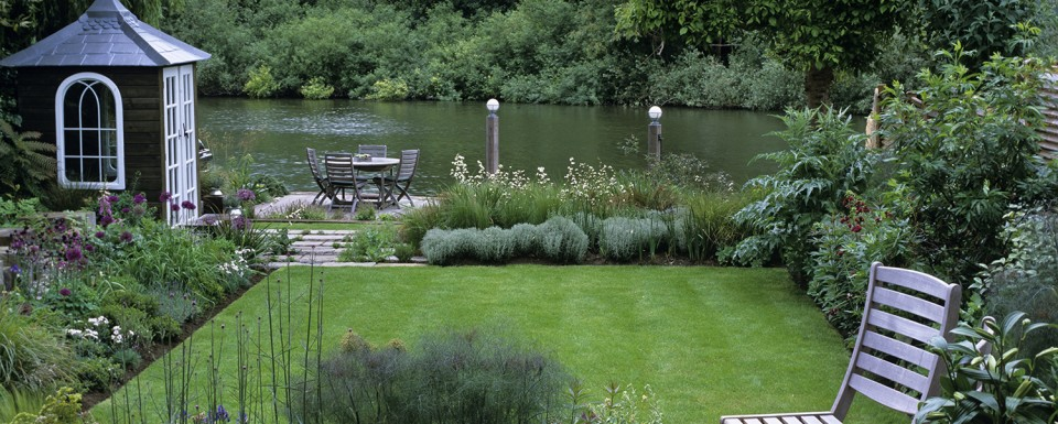 MAKEOVER. (Before: GOCK076) 25m x 11.5m garden 1 year after planting. View to river from lounge over deck, lawn, wave bed of grasses, santolina and libertia. Seating by water.