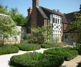 Beautiful House Featuring Path Surrounded By Square Beds Of Green Shrubs And Greenhouse