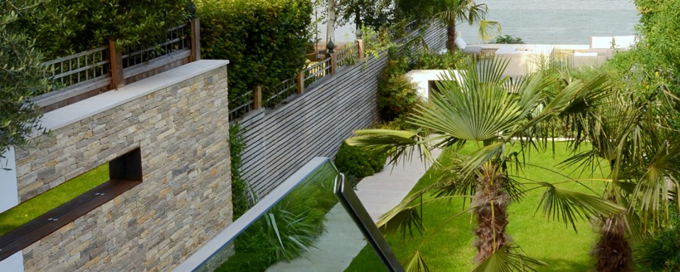 View over a sleek sophisticated garden looking down to the river at Putney