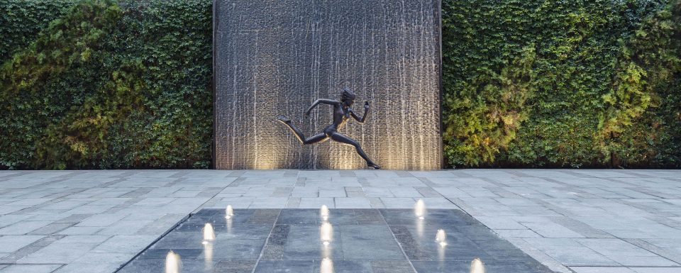 Female Statue Running With Waterfall Backdrop And Fountain